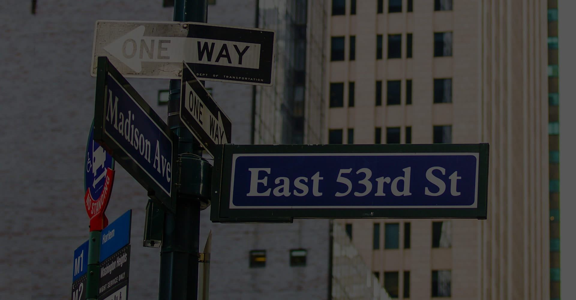 Photo of New York street signs, showing the location of Midtown Dental Excellence on Madison avenue.