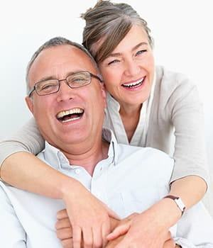Older couple laughing after receiving periodontics treatment.